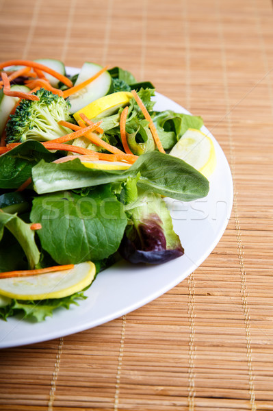 Fresh Vegetable Salad Half on Bamboo Placemat Stock photo © dbvirago