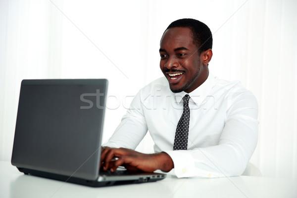 Сток-фото: смеясь · африканских · человека · используя · ноутбук · служба · счастливым