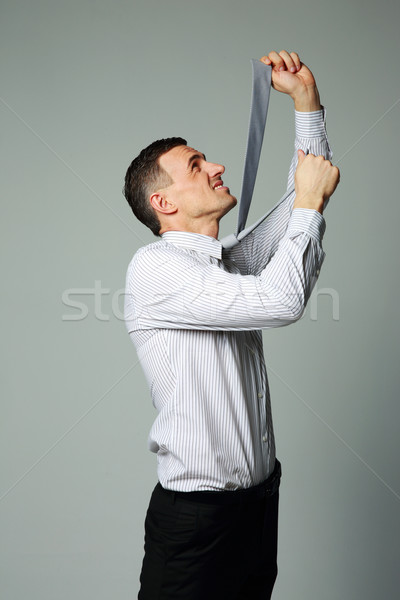 Businessman in suit hanging himself on tie on gray background Stock photo © deandrobot