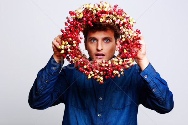 Funny man looking through a wreath over gray background Stock photo © deandrobot