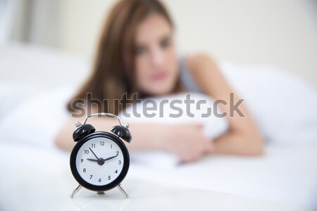 Woman waking up in the morning and looking on alarm clock. Focus on clock Stock photo © deandrobot