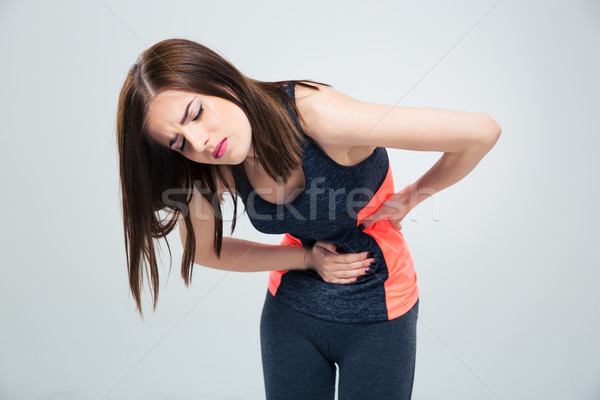 Fitness woman having pain in stomach Stock photo © deandrobot