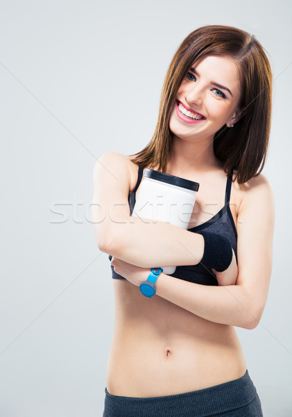 Happy sporty woman holding jar of protein Stock photo © deandrobot