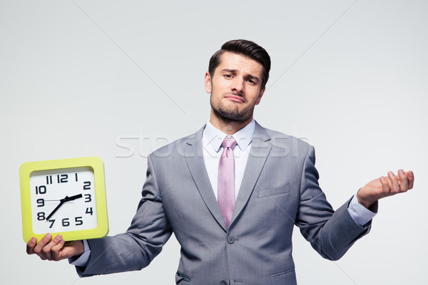 Businessman holding clock and copyspace  Stock photo © deandrobot