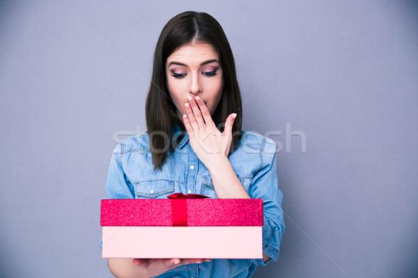 Meglepődött fiatal nő áll ajándék szürke néz Stock fotó © deandrobot