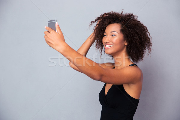 Smiling afro american woman making selfie photo Stock photo © deandrobot