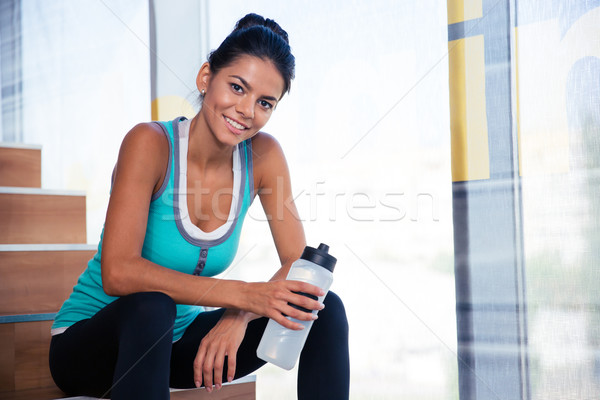 Woman resting on the stairs in gym Stock photo © deandrobot