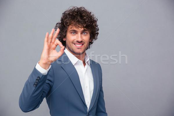 Smiling businessman showing ok sign Stock photo © deandrobot