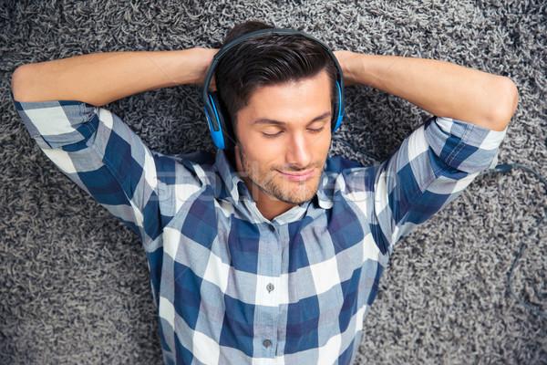 Man relaxing on the floor with headphones Stock photo © deandrobot