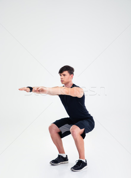 Fitness man doing squatting exercises Stock photo © deandrobot