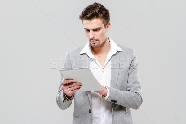 Concentrated young businessman using tablet Stock photo © deandrobot