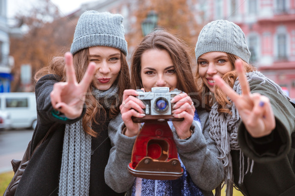 Three women making photo on camera outdoors Stock photo © deandrobot