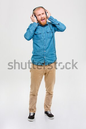 Excited amusing man listening to music using headphones and singing Stock photo © deandrobot