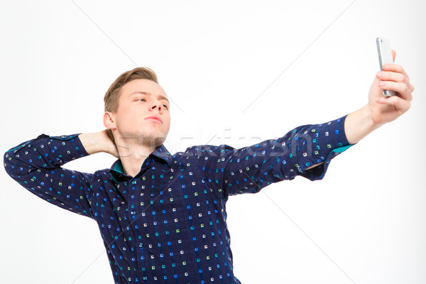 Confident amusing young male making selfie using cellphone Stock photo © deandrobot