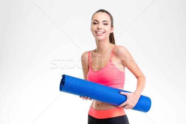 Portrait og smiling happy charming fitness girl with yoga mat Stock photo © deandrobot