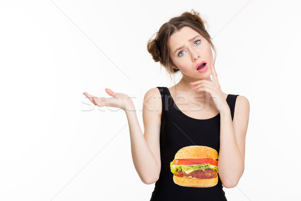 Amazed pretty young woman holding copyspace on palm  Stock photo © deandrobot