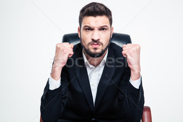 Angry annoyed bearded businessman sitting and showing fists  Stock photo © deandrobot