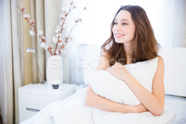 Happy woman waking up in bed and hugging white pillow Stock photo © deandrobot