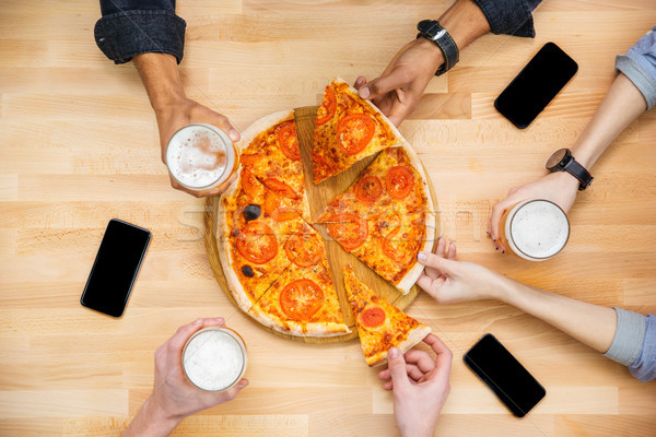 Friends tasting pizza and drinking beer on wooden table Stock photo © deandrobot
