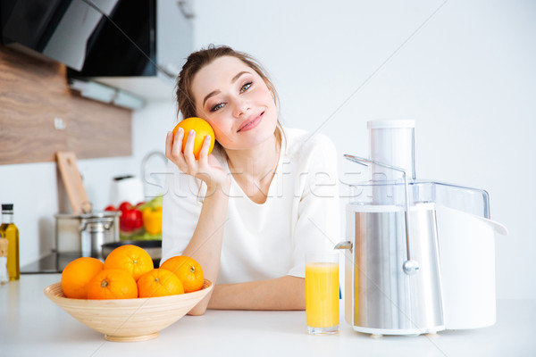 Lovely woman making orange juice on the kitchen Stock photo © deandrobot
