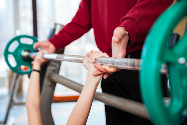 Fitness instructor supporting to woman athlete working out with barbell Stock photo © deandrobot