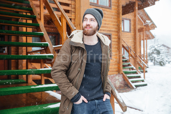 Pensive man standing near wooden cottage in snowy weather  Stock photo © deandrobot