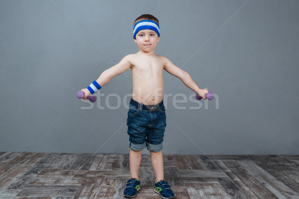 Cute little boy standing and working out using dumbbells Stock photo © deandrobot