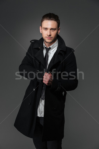 Confident businessman in black coat standing and posing Stock photo © deandrobot