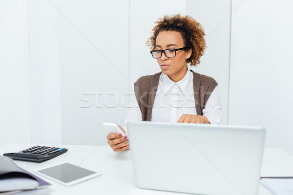 Grave african american donna ragioniere utilizzando il computer portatile smartphone Foto d'archivio © deandrobot