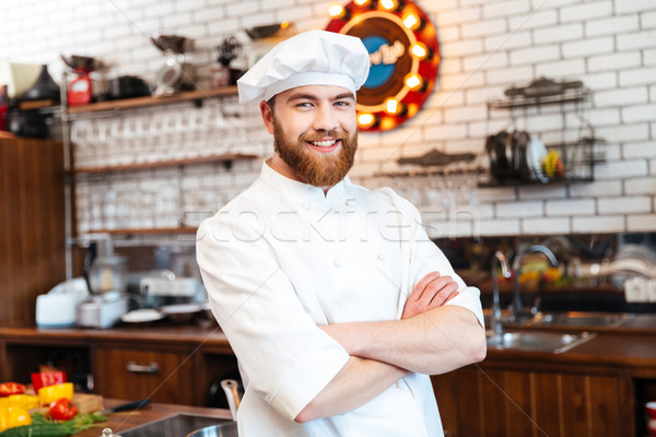 Cheerful chef cook standing with arms crossed on the kitchen Stock photo © deandrobot