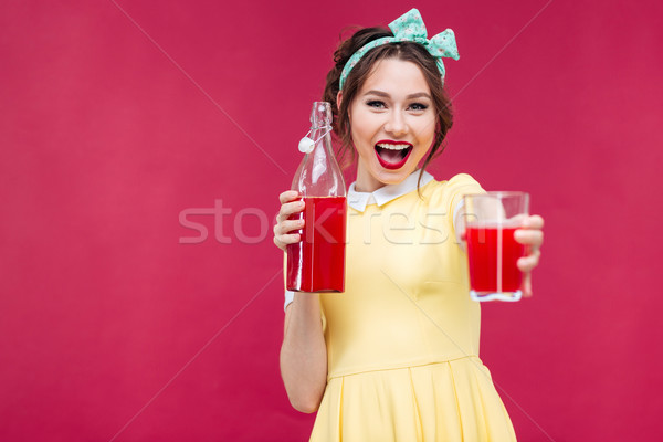 Happy beautiful pinup girl giving you a glass of juice Stock photo © deandrobot