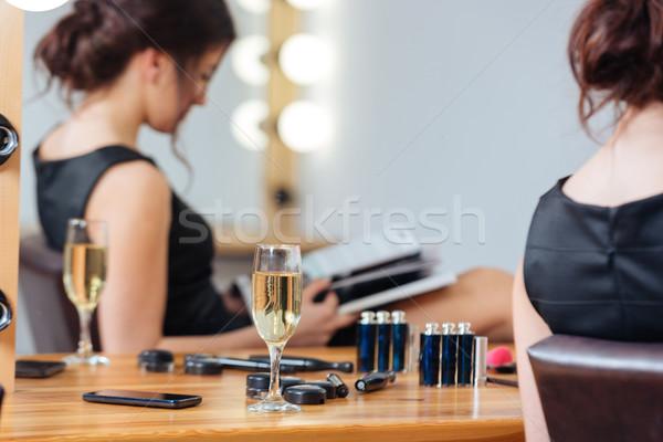 Vidrio champán pie mesa mujer lectura Foto stock © deandrobot