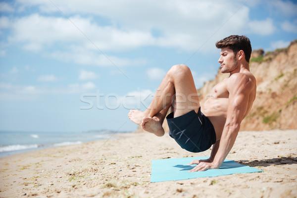 Férfi csukott szemmel gyakorol jóga tengerpart egyensúlyoz Stock fotó © deandrobot