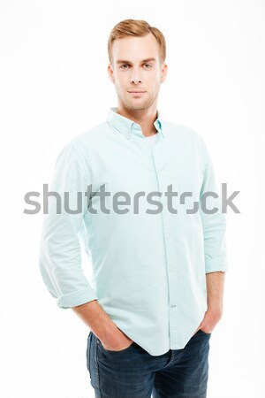 Serious attractive young man standing with hands in pockets Stock photo © deandrobot