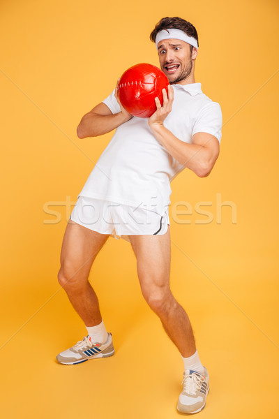 Full length portrait of a sportsman workout with fitness ball Stock photo © deandrobot