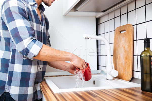 Man in checkered shirt washing dishes on the kitchen Stock photo © deandrobot