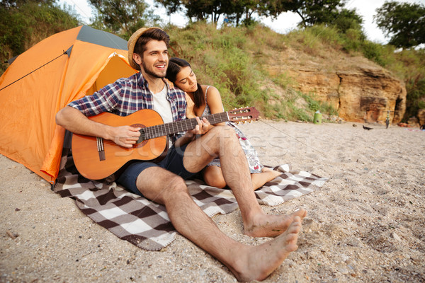 Young happy couple sitting at the tent and playing guitar Stock photo © deandrobot