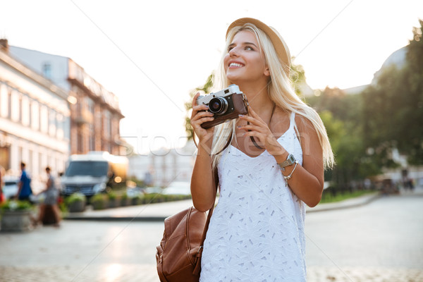 Happy woman with old vintage camera walking on the street Stock photo © deandrobot