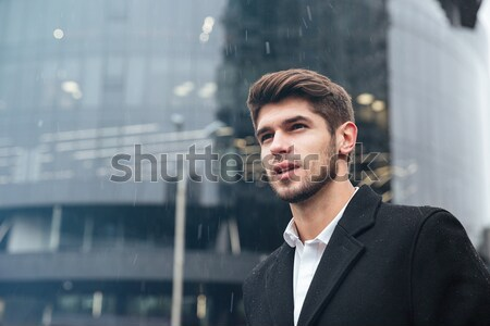 Stock photo: Portrait of a pensive businessman standing outdoors near office building