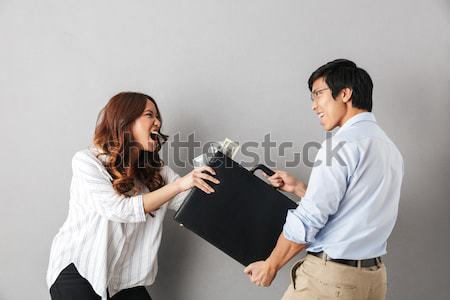 Angry man choking and threatening with gun to woman Stock photo © deandrobot