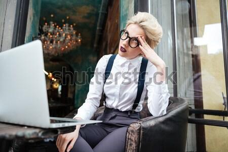 задумчивый женщину используя ноутбук чтение журнала кафе Сток-фото © deandrobot