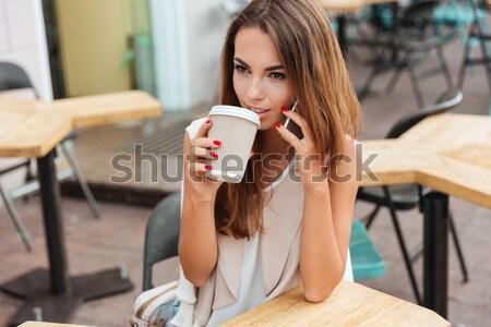 Uimit femeie frumoasa ceaşcă de cafea uita smartphone Imagine de stoc © deandrobot