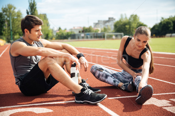 Stock photo: Athletic couple sitting and stretching legs together on stadium