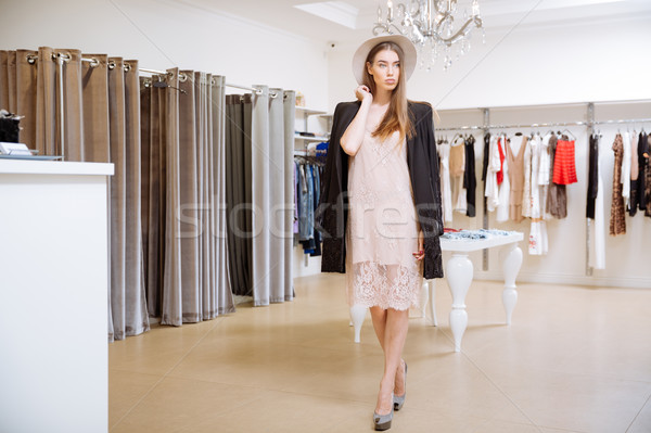 Fashionable woman standing in clothig shop Stock photo © deandrobot