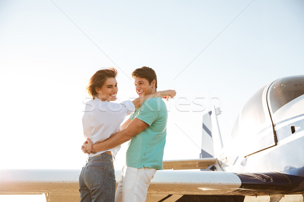 Couple hugging and laughing near private plane Stock photo © deandrobot