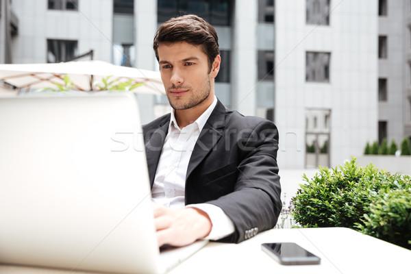 Empresario sesión usando la computadora portátil aire libre Servicio grave Foto stock © deandrobot