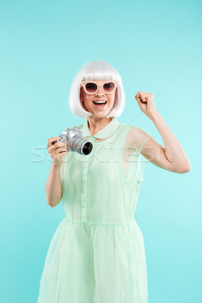 Cheerful young woman photographer holding photo camera and celebrating Stock photo © deandrobot