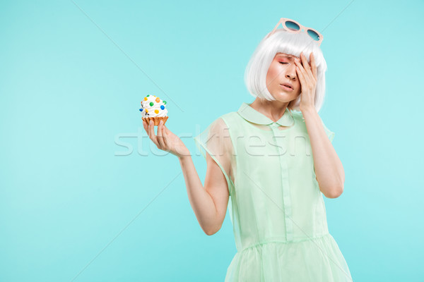 Unhappy depressed young woman stansing and holding cupcake Stock photo © deandrobot