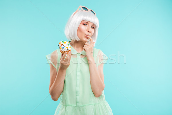Happy playful woman in blonde wig tasting cupcake by finger Stock photo © deandrobot