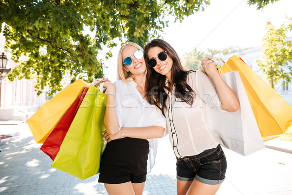 Two girls walking with shopping bags on city streets Stock photo © deandrobot